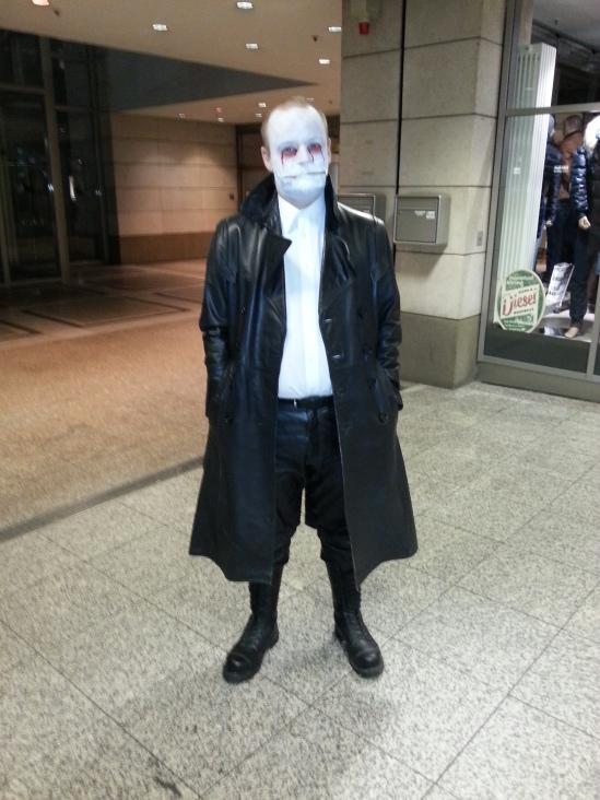 Mann in schwarzem Ledermantel, mit weißem Gesicht und Reissverschluß als Mund