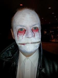 Weiß geschminktes Gesicht mit rot unterlaufenen und blutig aussehenden Augen. Statt eines Mundes ist nur ein geschlossener Reißverschluss zu sehen.