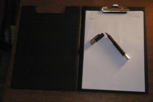 Ein Klemmbrett mit Papier und einem offenen Füller, bereit zum Schreiben.