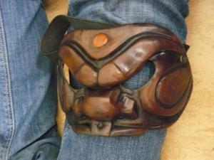 Arlecchino-Maske der Commedia dell'arte auf Knie