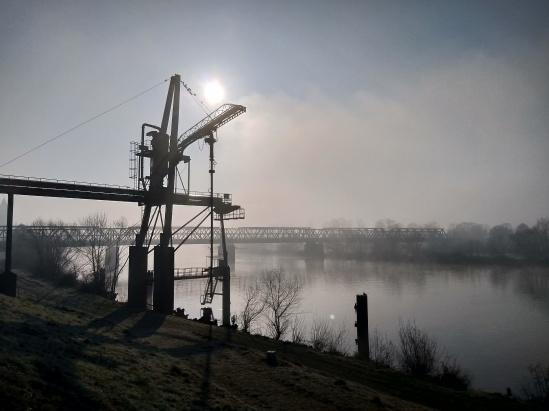Morgennebel am Fluss mit einem alten Kran und einer Eisenbahnbrücke im Hintergrund und der Sonne, die durch den Nebel leuchtet