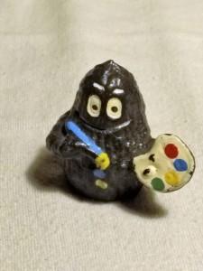 Schwarze Barbapapa-Figur mit Pinsel und Farbpalette in den Händen