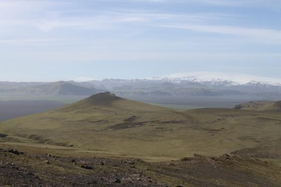 Landschaft, blasses Grün, leichte Erhebung, im Hintergrund schneebedeckte Erhöhungen