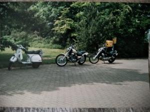 Ein weißer Roller, eine helle und eine blau Virago Motorräder) hintereinander geparkt.