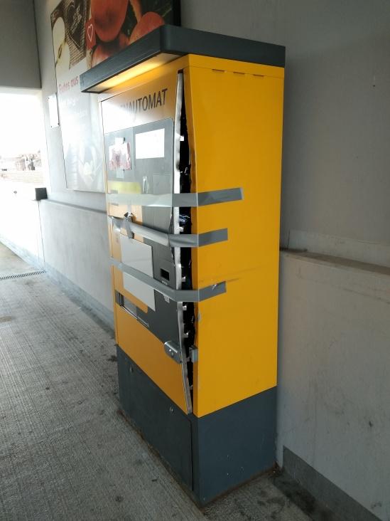 Parkautomat, dessen Vorderseite nur noch mit Klebestreifen festgehalten wird und mit einem Spalt absteht. Wahrscheinlich aufgebrochen oder gar gesprengt.