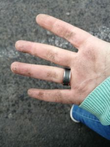 Dreckige Hand nach Graben in der Erde.