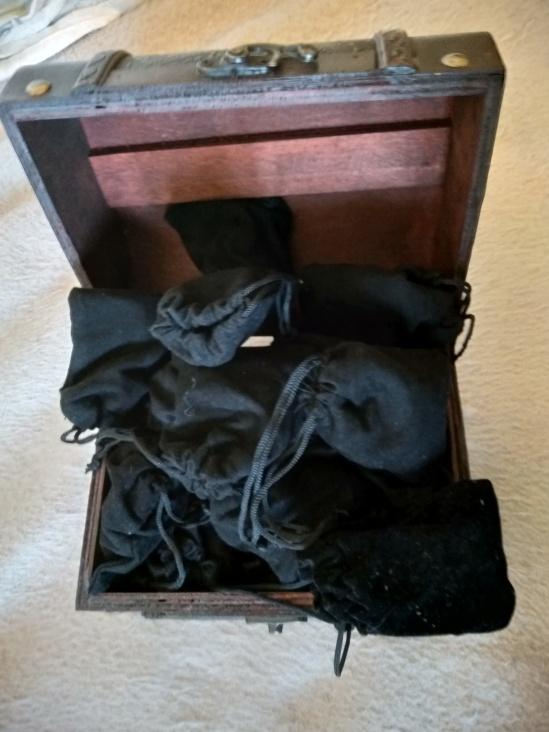 geöffnetes Holzkästchen mit Würfelsäckchen