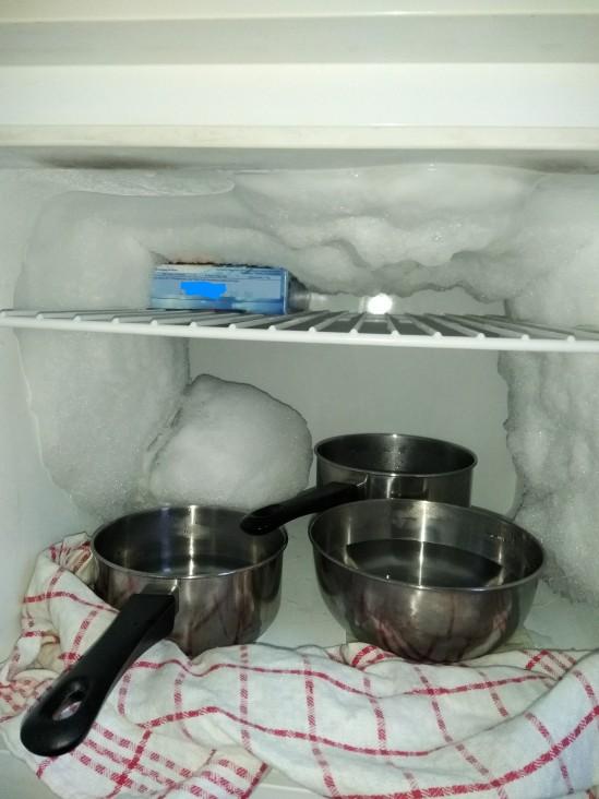 Eisfach mit dicker Eisschicht oben und an den Seiten. Unten stehen drei Behälter mit Wasser