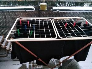 Wäscheständer mit schwarzer Wäsche zum Trocknen im Schnee auf dem Balkon