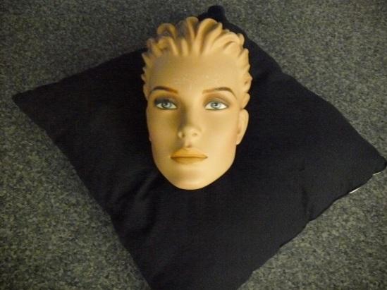Kopf einer Schaufensterpuppe auf einem schwarzen Kissen