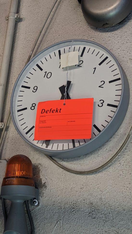 Wanduhr mit rotem aufgebrachten Zettel, auf dem DEFEKT steht.