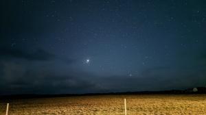 Ein Foto mit einem hellen Jupiter übe reiner Landschaft und ein paar anderen Sternen